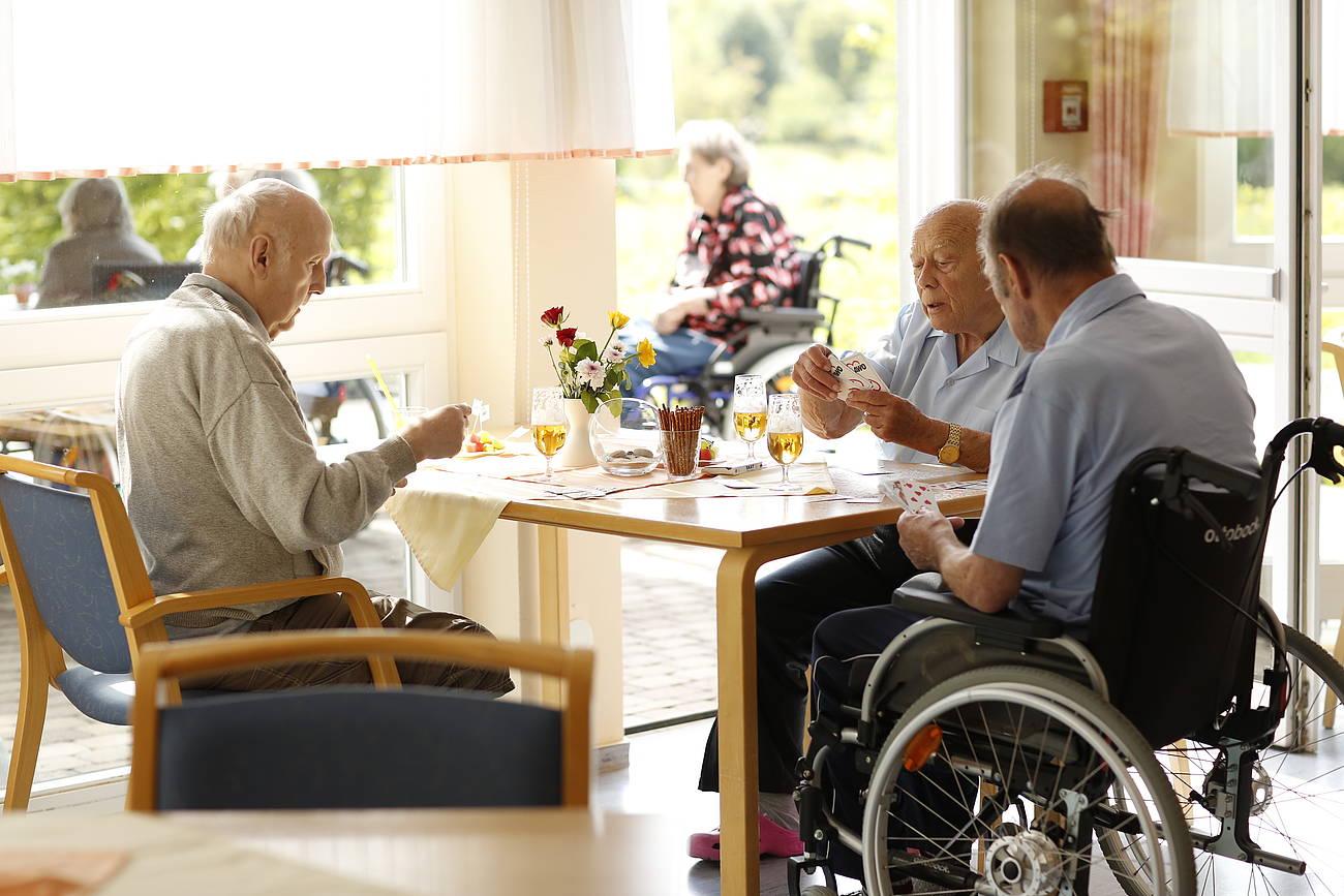 Bewohner spielen Karten am Tisch