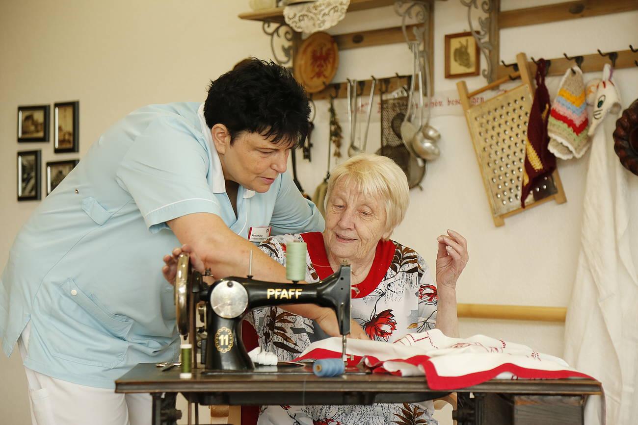 Seniorin mit Betreuerin an einer Nähmaschine