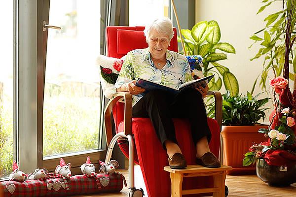Seniorin liest im Sessel